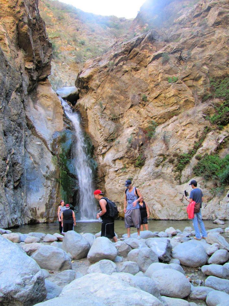 People walking around the base of Eaton Canyon Falls